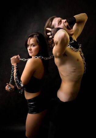 Pretty woman in leather clothing is holding a wired slave. Stock Photo - 4100082