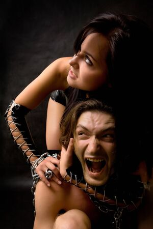 Pretty woman in leather clothing is holding a wired slave. Stock Photo - 4100119