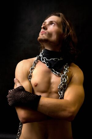 Naked muscular man in chain collar in the shadows. photo