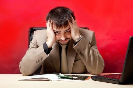 Portrait of businessman near laptop. Crisis theme. photo