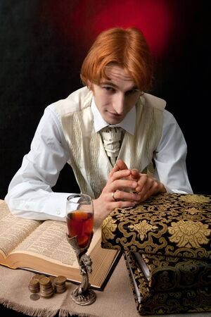 Portrait of handsome man with the glass of wine and old books. photo