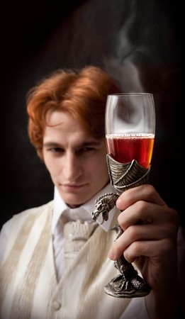 dragon vertical: Portrait of handsome man with the glass of flaming poisonous wine in ancient wineglass.