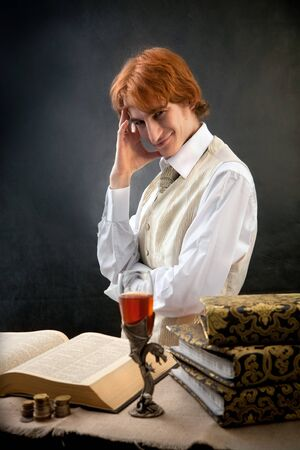 fop: Portrait of handsome man with the glass of wine and old books.