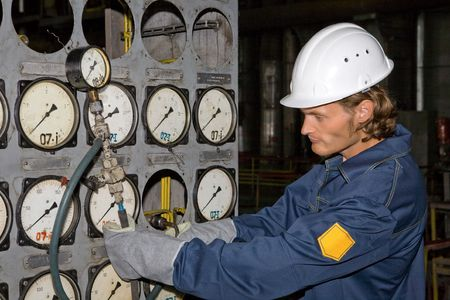 Yong worker in uniform is inspecting the pressure with a manometer photo