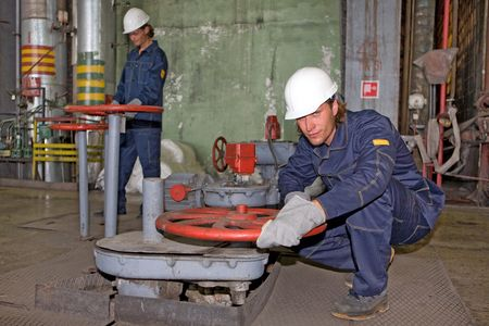 Yong workers in uniform are working on the factory
