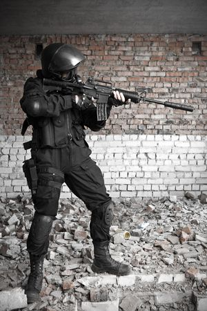 police body: Armed man in protective cask with M4 rifle (with muffler) on the ruined building background.