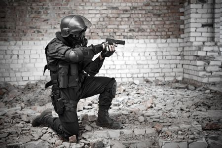 Armed man in protective cask with a pistol on the ruined building bagckround. Stock Photo