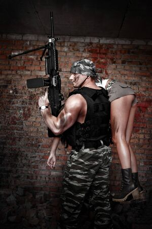 mercenary: Armed man with light machinegun on the ruined building background. Stock Photo