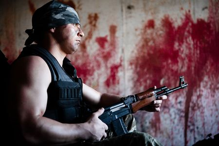 mercenary: Armed mercenary with submachine gun on the bloody wall background