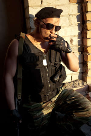 Armed muscular mercenary with cigar on the brick wall background Stock Photo - 4842525