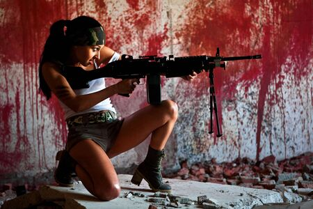 Aiming mercenary with light submachine gun on the bloody wall background.