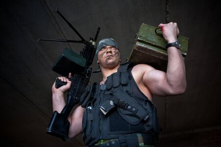 mercenary: Armed mercenary with submachine gun and box of grenade on the brick wall background