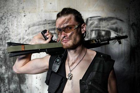 mercenary: Mercenary with sub machine gun on the painted wall background