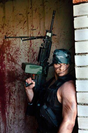 mercenary: Powerful mercenary with submachine gun on the grenade box. Stock Photo