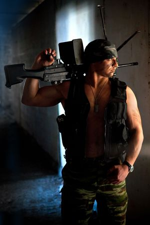 mercenary: Mercenary with submachine gun on the ruined building background Stock Photo
