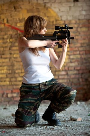 one armed: Armed woman with the rifle on the brick wall background.