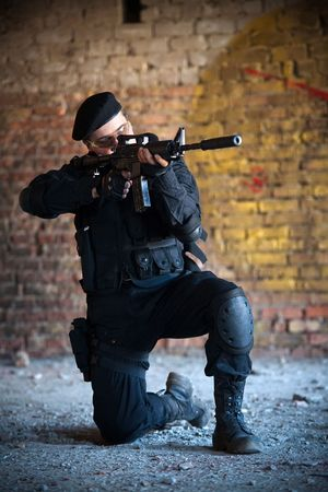Armed man with M4 rifle (with muffler) on the brick wall background.