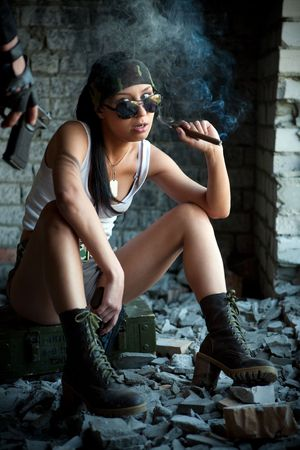 mercenary: Mercenary woman with a big cigar is looking on the pistol. Stock Photo