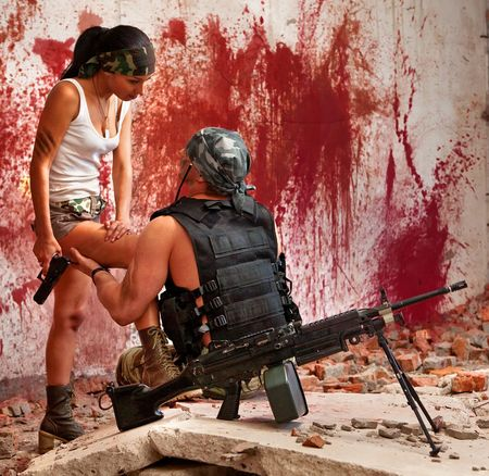 sexy army: Mercenary with the submachine gun and sexy girl on the bloody wall background Stock Photo