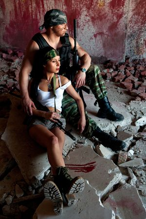 sexy army girl: Mercenary with M4 submachine gun and sexy girl on the bloody wall background Stock Photo