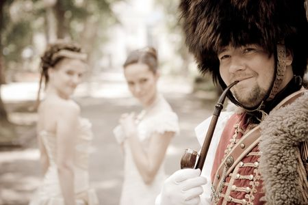 Russian hussar in vintage outfit is smoking his pipe. Two pretty women on the background are looking at him. photo