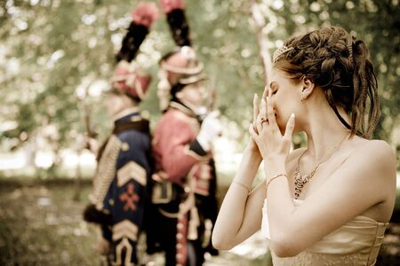 duel: Portrait of pretty crying woman dressed in vintage dress and accessories. Duelling hussars on the background.