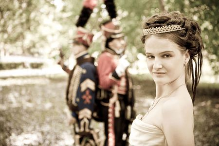 duelling: Portrait of pretty woman dressed in vintage dress and accessories. Duelling hussars on the background. Stock Photo