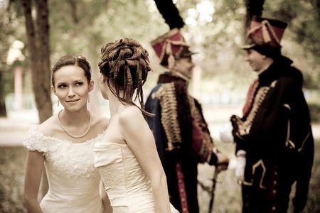 cavalryman: Dos vestidos de mujer bonita cosecha de vestir y accesorios est�n discutiendo hussars. Foto de archivo