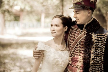cavalryman: Russian hussar in vintage outfit with pretty bride. Retro-styled photo.