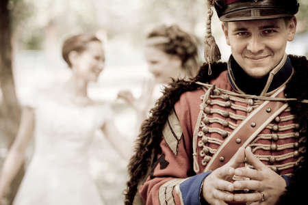 cavalryman: Smiling hussar in vintage outfit. Two pretty women on the background are discussing him.