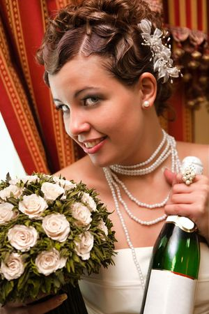 Pretty laughing bride with the rose bouquet and bottle of champaigne photo