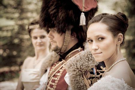 cavalryman: Ruso h�sar en traje de �poca con dos mujeres bonitas. Foto de archivo
