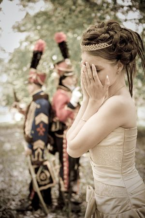 dueling: Portrait of pretty crying woman dressed in vintage dress and accessories. Dueling hussars on the background.
