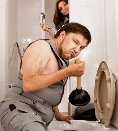 Angry plumber with the plunger in the bathroom.Girl with the shower on the background. Stock Photo