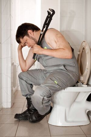 Thinking plumber with the adjustable wrench in the bathroom.  photo