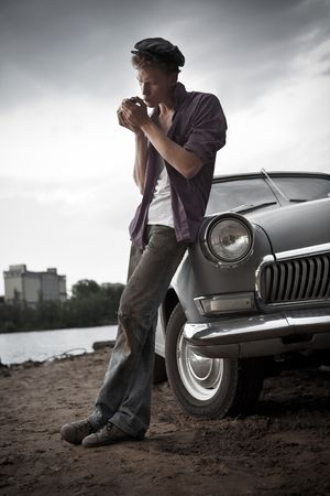 attitude: Smoking taxi driver near the vintage car. Retro-styled photo. Stock Photo