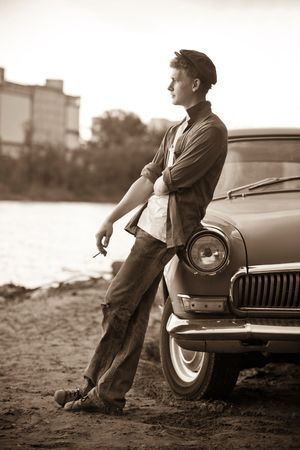 russian hat: Smoking taxi driver near the vintage car. Retro-styled photo. Stock Photo