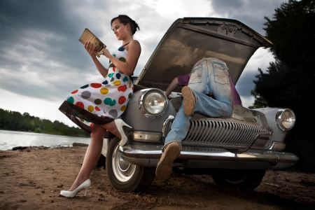 road assistance: Pretty couple is trying to repair their old car using manual. Rural background. Stock Photo