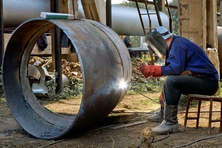 Welder in the mask and uniform is welding steel tubes.