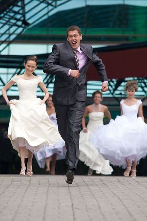 Laughing groom is escaping from the crowd of brides. photo