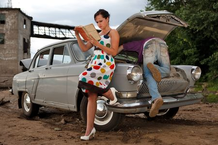 Pretty couple is trying to repair their old car using manual. Rural background. Archivio Fotografico