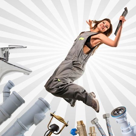 guarniciones: Bastante fontanero saltando con la llave ajustable. Grifos, tuber�as, mangueras, accesorios, sif�n en la periferia. Foto de archivo