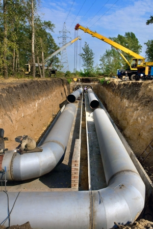 drain: A group of workers are constructing a trunk pipeline in the ditch. Stock Photo