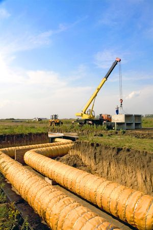 A group of workers are constructing a trunk pipeline in the ditch. Stock Photo