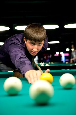 Man is playing billiard. Focus point on the face. photo