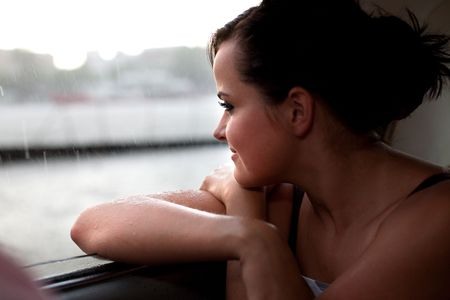 Pretty girl is sitting on the back seat of a car. Rainy weather on the background. photo