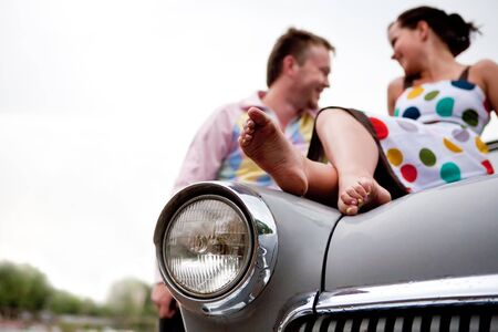 Pretty couple is relaxing on the vintage car foreground. photo