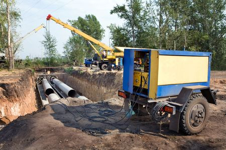 electricity generator: A group of workers are constructing a trunk pipeline in the ditch. Stock Photo