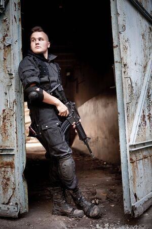 Brave sentinel with M4 carbine near the rusty gates.