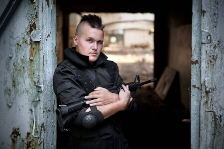 Warrior with the M4 rifle on the ruined building background. photo
